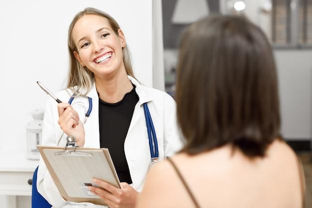 Femme médecin expliquant le diagnostic à sa jeune femme patiente. Photo gratuit
