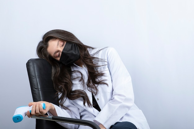 Femme Médecin En Masque Médical Tenant Un Thermomètre Et Dormir Sur Une Chaise. Photo gratuit