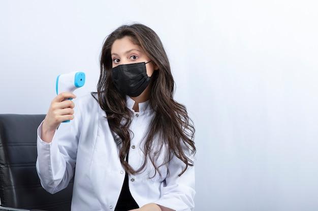 Femme Médecin En Masque Médical Tenant Un Thermomètre Et Regardant à L'avant. Photo gratuit