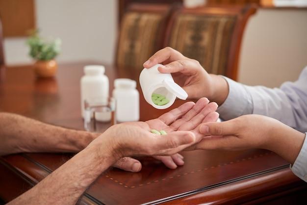 Femme médecin méconnaissable donnant des pilules à un patient lors d'une visite à domicile Photo gratuit