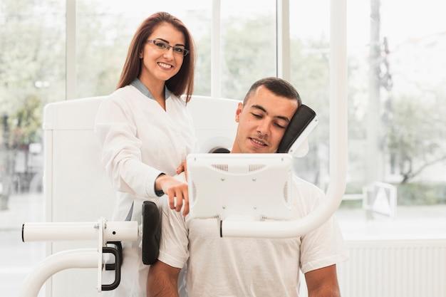 Femme médecin montrant au patient comment utiliser un appareil médical Photo gratuit