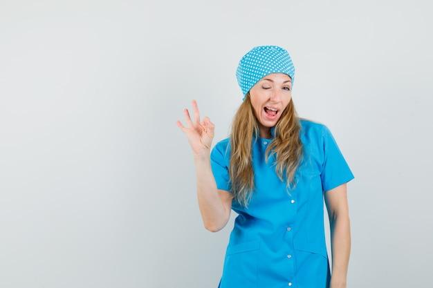 Femme Médecin Montrant Un Geste Ok Et Un Clin D'œil En Uniforme Bleu Photo gratuit