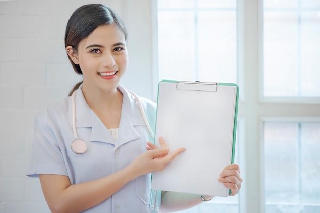 Femme médecin montrant le presse-papiers avec la surface. Photo Premium