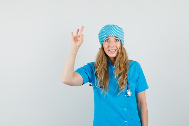 Femme Médecin Montrant Signe Ok En Uniforme Bleu Et à La Joyeuse Photo gratuit