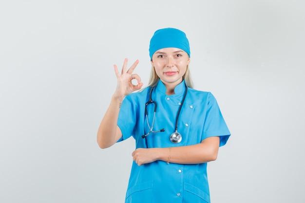 Femme Médecin Montrant Signe Ok En Uniforme Bleu Et à La Satisfaction. Photo gratuit