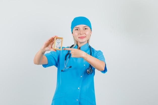 Femme Médecin Pointant Le Doigt Sur Le Sablier En Uniforme Bleu Et à La Bonne Humeur. Photo gratuit