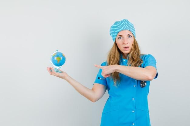 Femme Médecin Pointant Sur Globe En Uniforme Bleu Photo gratuit
