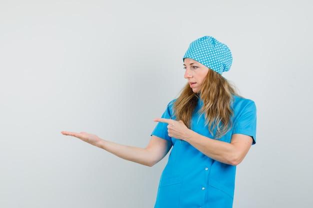 Femme Médecin Pointant Sur La Paume écartée En Uniforme Bleu Photo gratuit