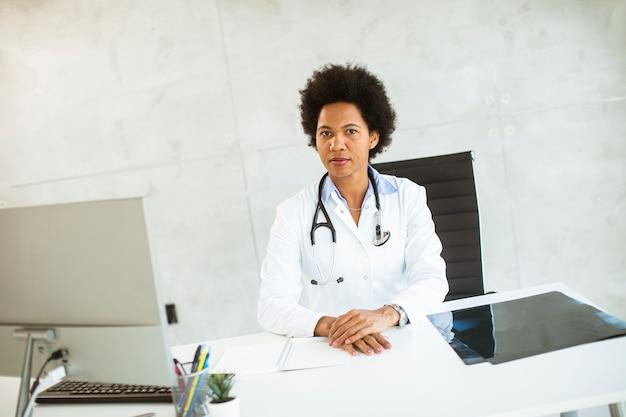 Femme Médecin Portant Une Blouse Blanche Avec Stéthoscope Assis Derrière Un Bureau Au Bureau Photo Premium
