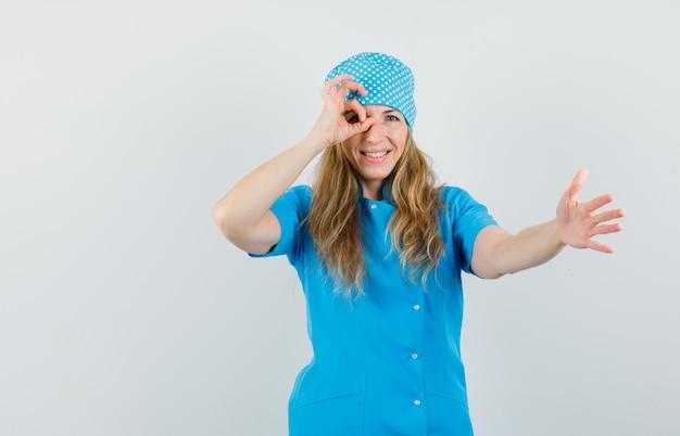 Femme Médecin Qui S'étend De La Main Avec Signe Ok Sur Les Yeux En Uniforme Bleu Et à La Bonne Humeur. Photo gratuit