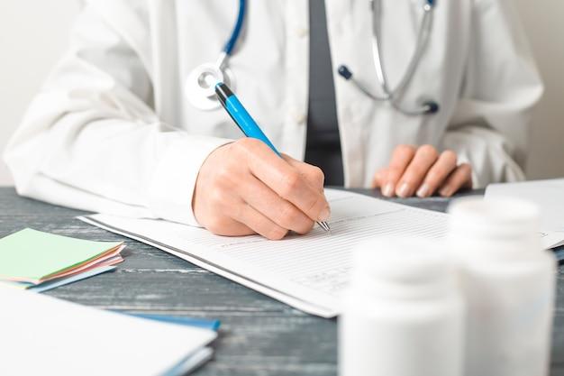 Une femme médecin rédige un rapport médical dans le bureau de la clinique. Photo Premium