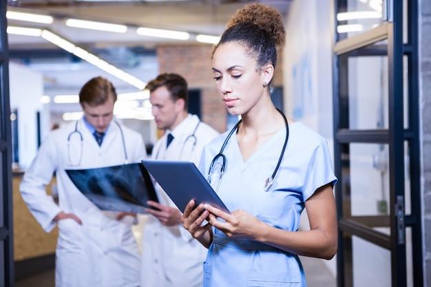 Femme médecin regardant une tablette numérique à l'hôpital et ses collègues debout derrière et discutant Photo Premium