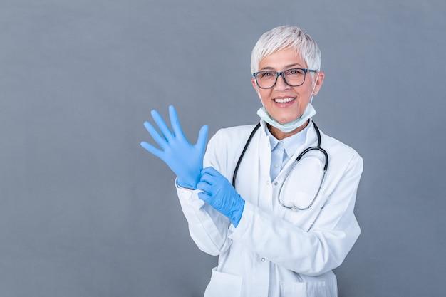 Femme Médecin Senior Mettant Des Gants De Protection, Isolé Sur Le Mur. Docteur, Mettre, Stérile, Gants Photo Premium