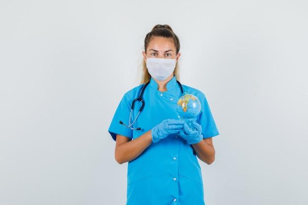 Femme Médecin Tenant Le Globe Terrestre En Uniforme Bleu, Masque, Gants Et Regardant Attentivement. Photo gratuit