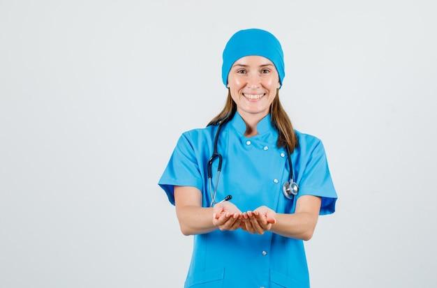 Femme Médecin Tenant La Main En Forme De Coupe En Uniforme Bleu Et à La Joyeuse. Vue De Face. Photo gratuit