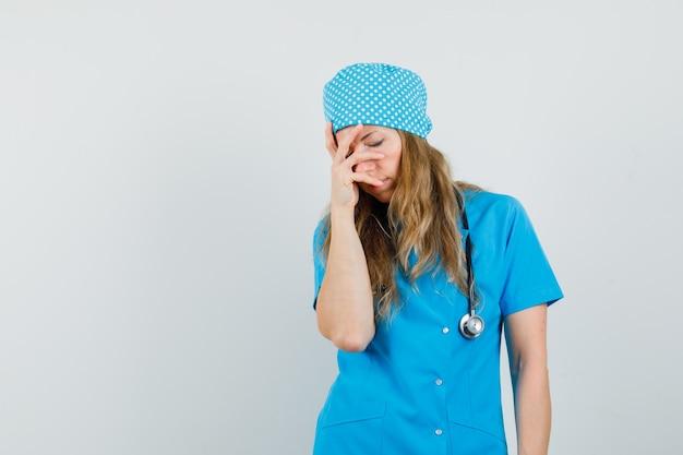 Femme Médecin Tenant La Main Sur Le Visage En Uniforme Bleu Et L'air Fatigué. Photo gratuit