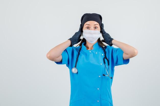Femme Médecin Tenant Les Mains Sur Les Oreilles En Uniforme, Gants, Masque Et à La Peur Photo gratuit