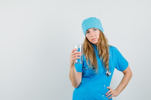 Femme Médecin Tenant Une Tasse à Mesurer En Uniforme Bleu Photo gratuit