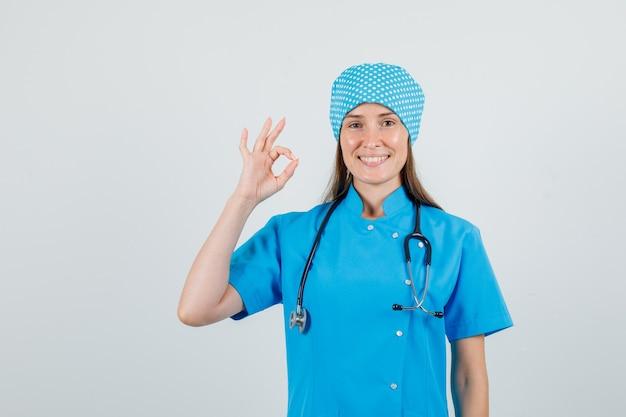 Femme Médecin En Uniforme Bleu Montrant Le Geste Ok Et à La Bonne Humeur Photo gratuit