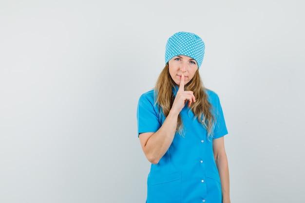 Femme Médecin En Uniforme Bleu Montrant Le Geste De Silence Et à La Prudence Photo gratuit