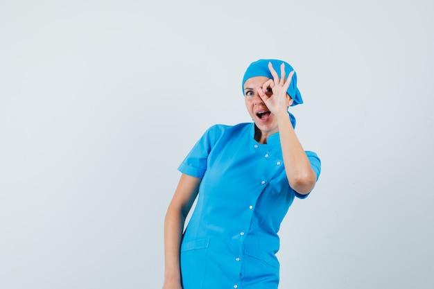 Femme Médecin En Uniforme Bleu Montrant Signe Ok Sur L'oeil Et à La Vue étonnée, De Face. Photo gratuit