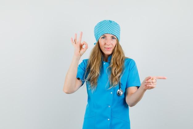 Femme Médecin En Uniforme Bleu Montrant Signe Ok Tout En Pointant Vers Le Côté Et à La Joyeuse Photo gratuit