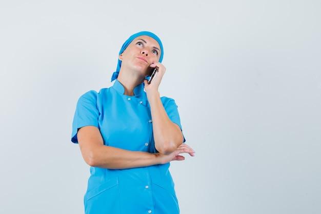 Femme Médecin En Uniforme Bleu, Parler Au Téléphone Mobile Et à La Vue Réfléchie, De Face. Photo gratuit
