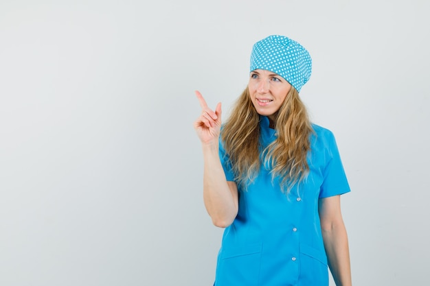 Femme Médecin En Uniforme Bleu Pointant Vers Le Haut Et à La Joyeuse Photo gratuit