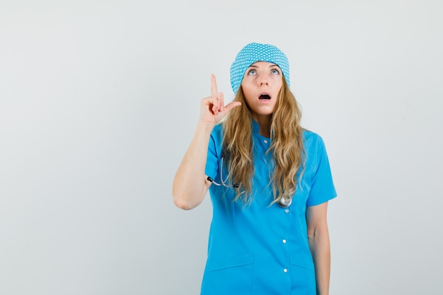 Femme Médecin En Uniforme Bleu Regardant Avec Le Doigt Vers Le Haut Et à La Surprise Photo gratuit