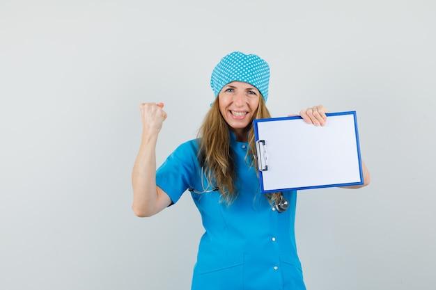 Femme Médecin En Uniforme Bleu Tenant Le Presse-papiers Avec Le Geste Du Gagnant Et L'air Heureux Photo gratuit