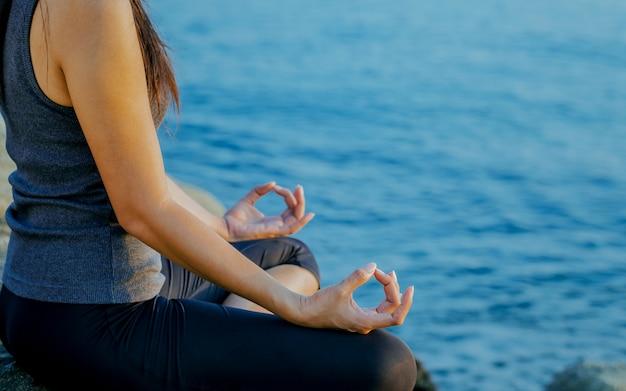 La femme méditant dans une pose de yoga sur la plage tropicale. Photo Premium