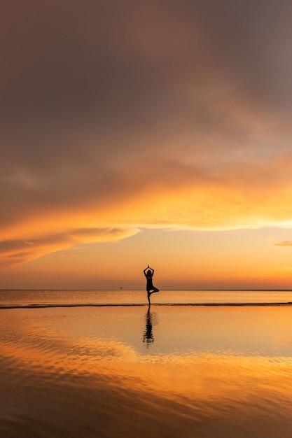 Femme De Méditation Pratiquant Le Yoga De L'arbre Pose Sur La Plage Au Coucher Du Soleil Photo Premium