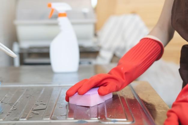 Femme de ménage nettoyant évier dans la cuisine avec éponge et nettoyant. Photo Premium