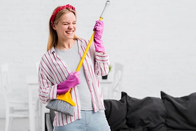 Femme De Ménage S'amusant Avec Une Brosse Photo gratuit