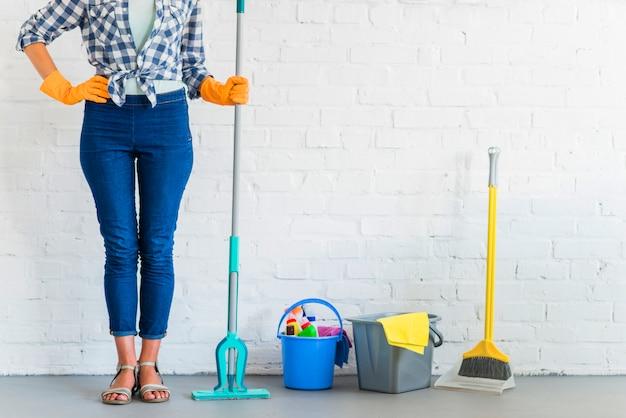 Femme de ménage tenant une vadrouille près des équipements de nettoyage devant le mur de briques Photo gratuit