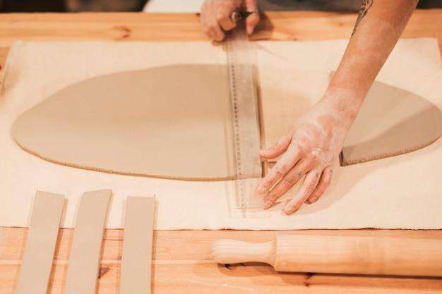 Femme mesurant l'argile avec une règle en plastique sur la table Photo gratuit