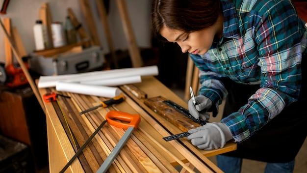 Femme Mesurant Des Planches De Bois Photo gratuit