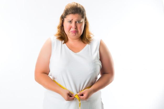 Femme mesurant sa taille avec du ruban adhésif Photo Premium