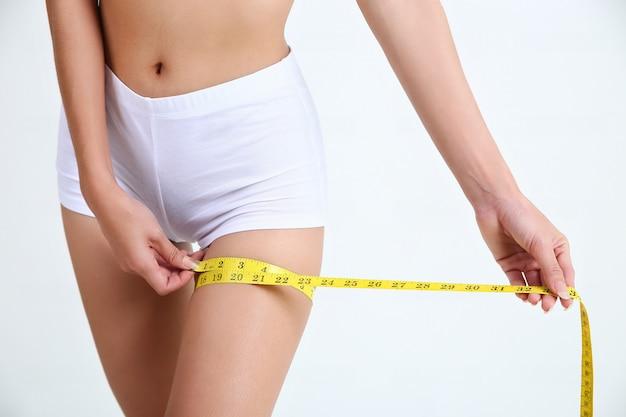 Femme mesurant la taille de la cuisse et des jambes avec du ruban à mesurer Photo gratuit