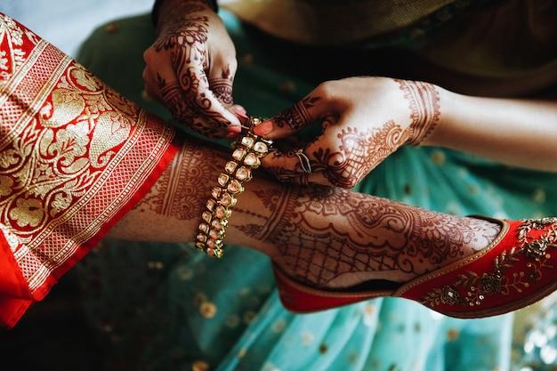 Femme met le bracelet sur la jambe de la mariée hindoue Photo gratuit