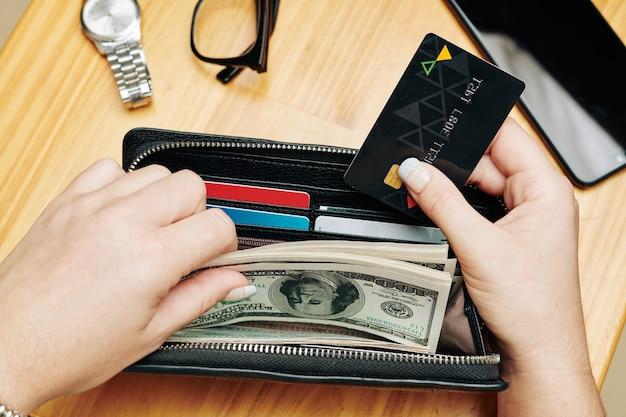 Femme Mettant La Carte Et L'argent Dans Le Sac à Main Photo Premium