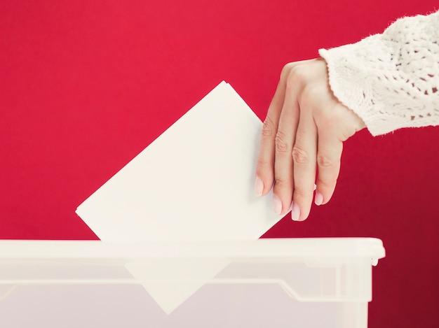 Femme mettant une carte maquette dans une boîte pour l'élection Photo gratuit