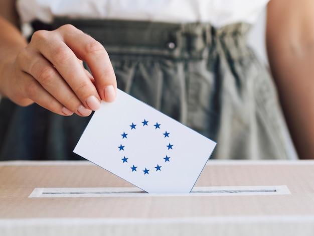 Femme mettant son bulletin de vote dans une boîte Photo gratuit