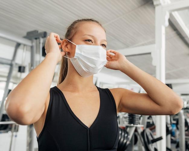 Femme Mettant Son Masque Médical Au Gymnase Photo gratuit