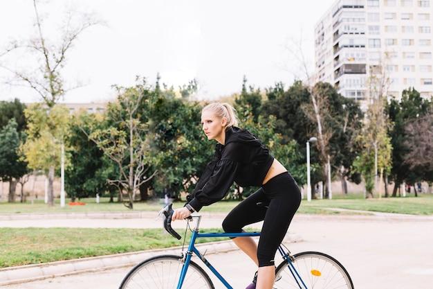 Femme mince e \ équitation vélo dans le parc Photo gratuit