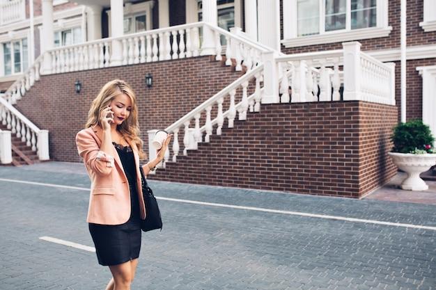 Femme à La Mode Aux Cheveux Longs Marchant En Robe Noire Sur Rue Sur Fond De Maison Royale. Elle Parle Au Téléphone, Regarde Vers Le Bas. Photo gratuit