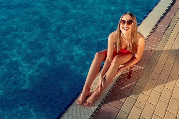 Femme à La Mode En Bikini Rouge Assis Près De La Piscine Photo Premium
