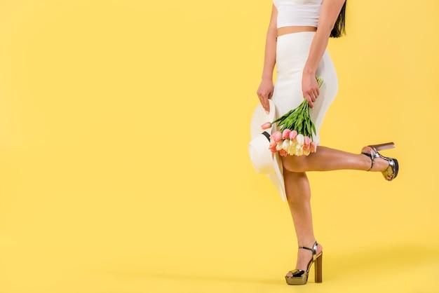 Femme à la mode avec bouquet de tulipes Photo gratuit