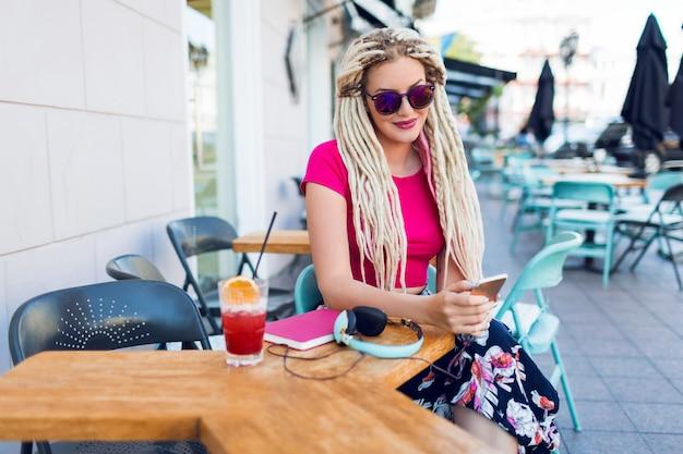 Femme à La Mode Avec Des Dreadlocks Utilisant Un Téléphone Intelligent, Publie Des Photos, Lisant Des Nouvelles Et Buvant Un Délicieux Smoothie Rose. Porter Une Tenue D'été Lumineuse. Café De La Ville. Photo gratuit
