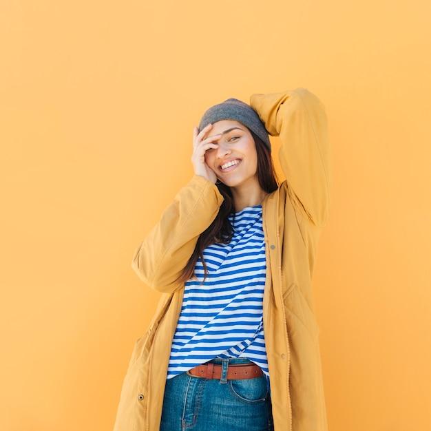 Femme à la mode portant veste sur t-shirt rayé posant tout en regardant la caméra Photo gratuit